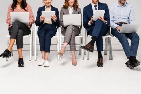 Photo pour Vue recadrée de gens d'affaires multiethniques souriants utilisant des appareils sur des chaises sur fond gris - image libre de droit