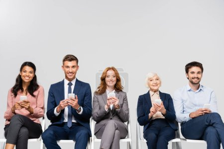 Photo for Smiling multicultural businesspeople using smartphones isolated on grey - Royalty Free Image