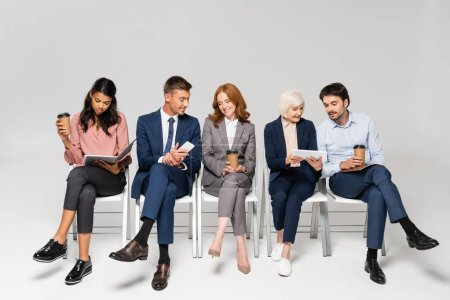 Multiethnic businesspeople with coffee to go using devices on chairs on grey background