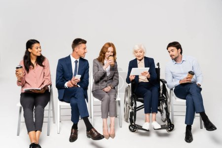 Photo for Smiling multiethnic businessman with coffee to go and paper folders sitting near elderly businesswoman in wheelchair on grey background - Royalty Free Image