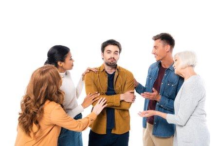 Photo pour Triste homme aux bras croisés se tenant près d'amis multiethniques isolés sur blanc - image libre de droit