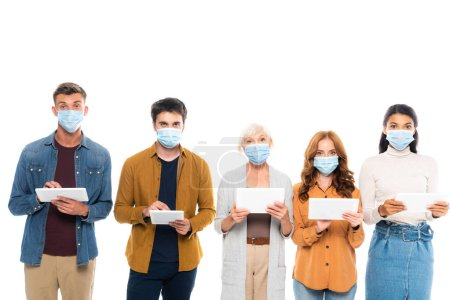 Photo for Multicultural people wearing medical masks and using digital tablets isolated on white - Royalty Free Image