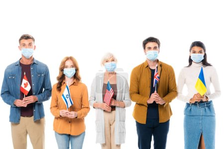 Multicultural people in medical masks looking at camera while holding flags isolated on white