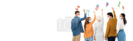 Multiethnic friends in medical masks holding flags of countries isolated on white, banner