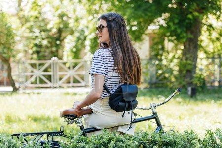 Photo pour Vue arrière du jeune à lunettes de soleil assis sur le vélo rétro et parler sur smartphone dans le parc - image libre de droit