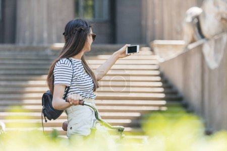 side view of young attractive woman in sunglasses taking selfie on smartphone on street
