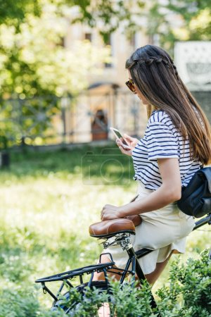 Photo for Side view of young attractive woman using smartphone while leaning on bicycle in park - Royalty Free Image