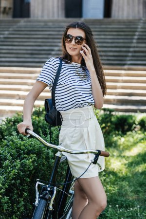 young pretty woman in sunglasses with retro bicycle talking on smartphone