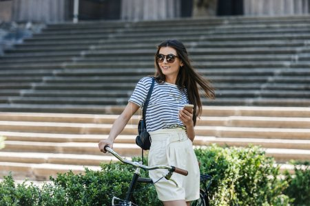 portrait of young smiling woman with smartphone and retro bicycle on street