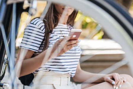 partial view of woman using smartphone while sitting near retro bicycle on street