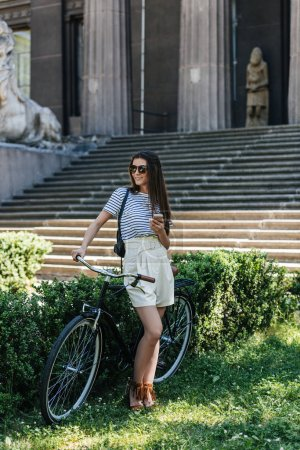 young attractive woman with smartphone and retro bicycle standing on street