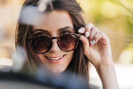 Photo for Portrait of of beautiful young woman in sunglasses on street - Royalty Free Image