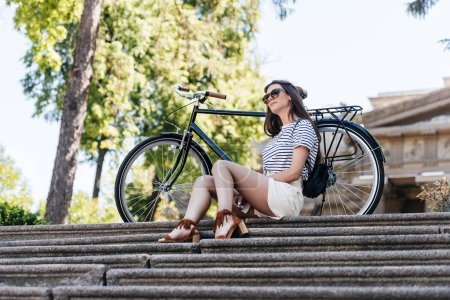 stylish young woman in sunglasses with retro bicycle resting on steps