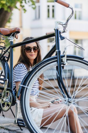 portrait of young smiling woman with smartphone sitting near retro bicycle on street