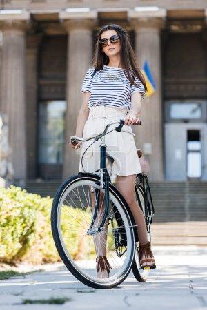 élégante jeune femme à lunettes de soleil vélo rétro se tenant debout sur la rue
