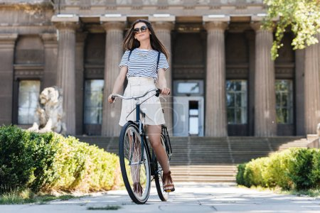 stylish young woman in sunglasses with retro bicycle standing on street