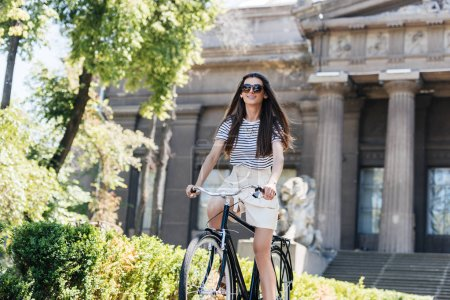 Photo for Young smiling woman in sunglasses riding retro bicycle on street - Royalty Free Image