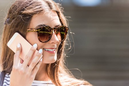 Photo for Portrait of young pretty woman in sunglasses talking on smartphone - Royalty Free Image