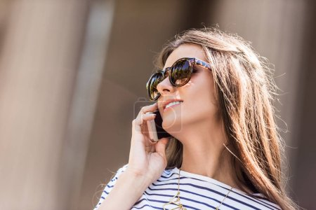 portrait of young pretty woman in sunglasses talking on smartphone