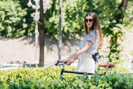 Photo pour Vue latérale d'une élégante jeune femme à lunettes de soleil avec rétro vélo dans le parc - image libre de droit