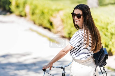 side view of young smiling woman in sunglasses with retro bicycle on street