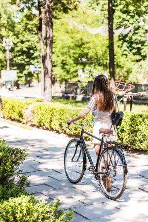 Photo pour Vue arrière du femme avec rétro vélo marche sur la rue - image libre de droit