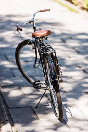 close up view of black retro bicycle parked on street