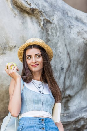 portrait of young stylish woman in hat with fresh apple on street