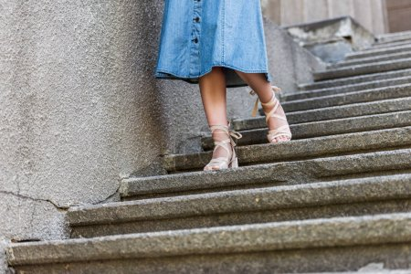 cropped shot of woman in denim skirt and stylish shoes walking down steps