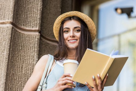pretty smiling woman with opened book and coffee to go on street