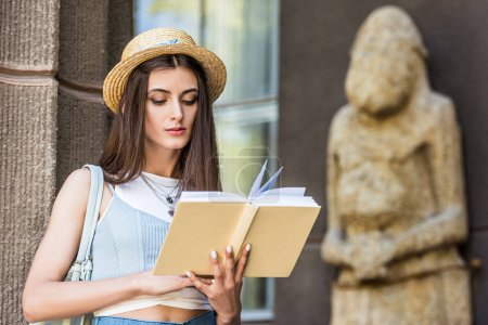 portrait of student in straw hat reading book on street