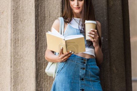 partial view of pretty young woman reading book and coffee to go on street