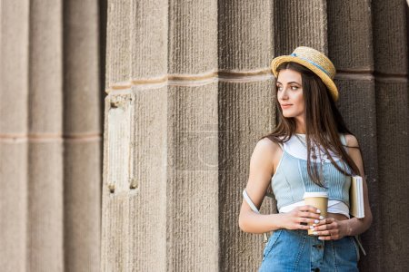 portrait of young pensive woman with book and coffee to go on street