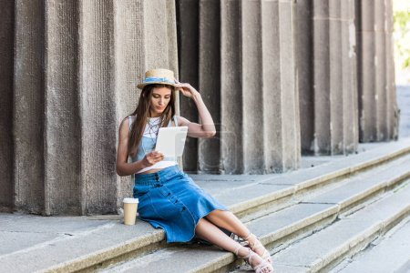 Photo for Young woman with coffee to go using tablet while sitting on steps - Royalty Free Image
