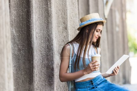Photo for Portrait of young woman with coffee to go using tablet on street - Royalty Free Image