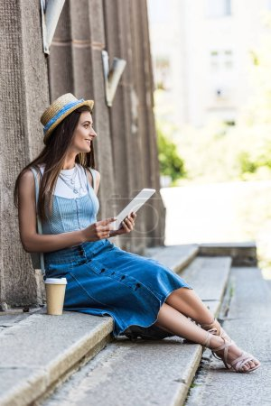 young smiling woman with tablet and coffee to go resting on steps on street