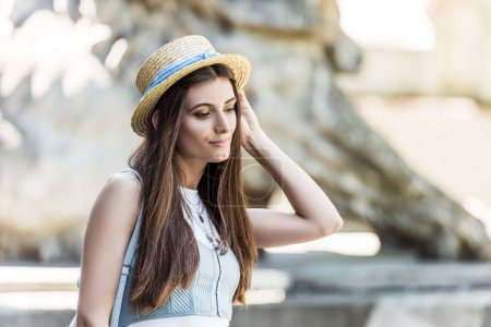 portrait of young thoughtful woman in straw hat on street