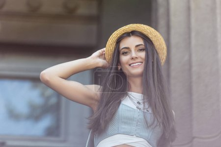 Photo for Portrait of beautiful smiling woman in straw hat on street - Royalty Free Image