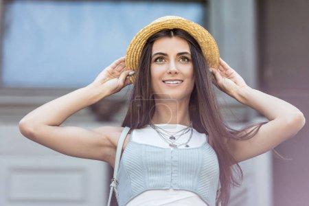 portrait of beautiful smiling woman in straw hat on street