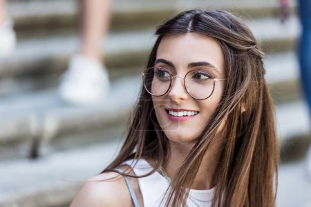 portrait of attractive smiling woman in eyeglasses on street