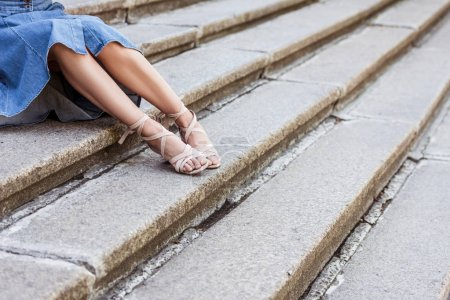 cropped shot of woman in denim skirt and fashionable shoes resting on steps on street