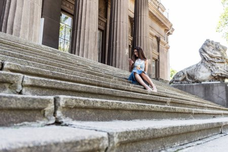 young woman using smartphone while resting on steps on street