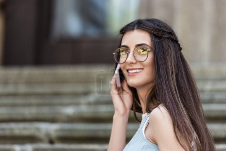 young smiling woman in eyeglasses talking on smartphone on street