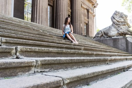 young stylish woman in eyeglasses and denim skirt resting on steps on street