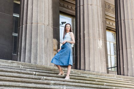 young stylish woman in eyeglasses and denim skirt standing on steps