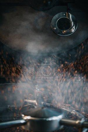 Photo pour Cuire à la vapeur chaude des grains de café durant la torréfaction processus en machine professionnelle - image libre de droit