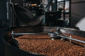 Interior of coffee production workshop with working coffee roasting machine
