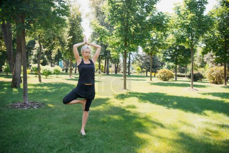 woman practicing yoga in Tree pose (Vrksasana) on grass in park