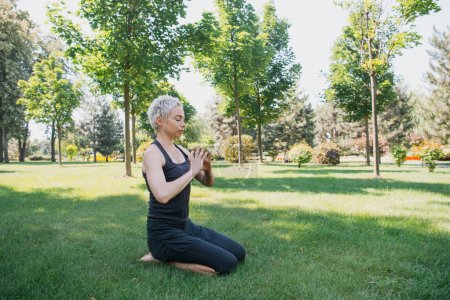 woman practicing yoga and making gesture with hands on grass in park