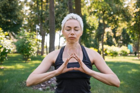 Photo pour Femme méditant les yeux fermés dans le parc - image libre de droit